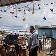 Dennis Sinnok, who works for Raven airlines, grills hamburgers and hot dogs for a Sunday afternoon barbecue, outside his home in the village of Shishmaref, Alaska, an Inupiat community of about 600 people near the Bering Strait.  Shishmaref is one of at least 31 Alaska Native villages under imminent threat due to climate change, according to a 2009 report from the Government Accountability Office. Shishmaref is steadily disappearing because of erosion and flooding due to climate change. Only one quarter mile wide and two and half miles long, Shishmaref has been  grappling with rising sea levels that have eroded more than 200 feet of the village, since 1969, according to a relocation study published in February. Climate change has resulted in a reduction in the sea ice which buffers Shishmaref from storm surges. At the same time, the permafrost that the village is built on has also begun to melt, making the shore even more vulnerable to erosion.