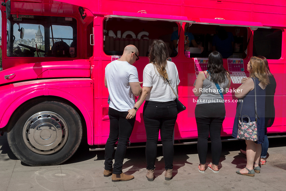 Customers choose what to buy from the pink double-decker Routemaster bus of yoghurt retailer Snog, on the Southbank, on 9th May 2018, in London, England.