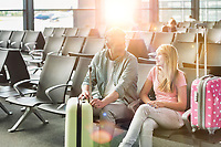 Portrait of mature man talking to her daughter while waiting and sitting in airport with yellow lens flare