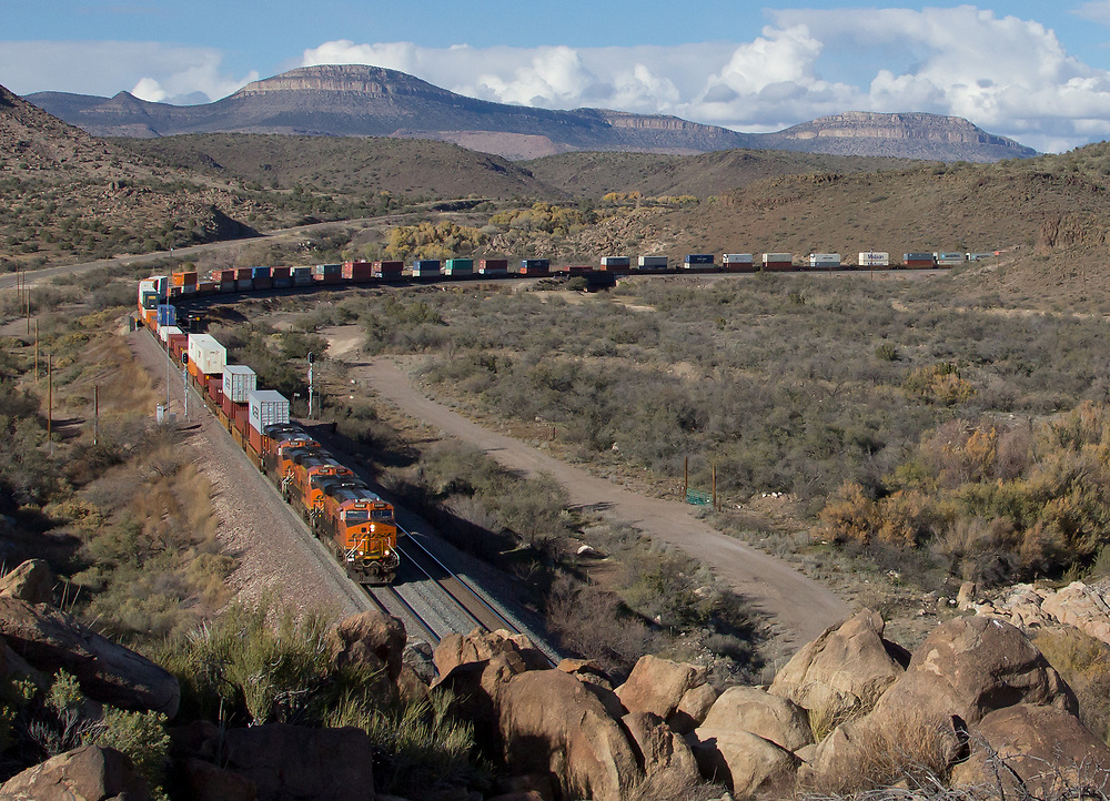 A heavy westbound intermodal slowly moves out of Crozier Canyon as it rounds the Valentine Curve with Laughing Jack Peak towering in the background. Nov. 27, 2015.