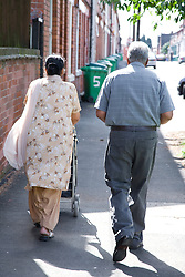 Older couple walking down a street together,