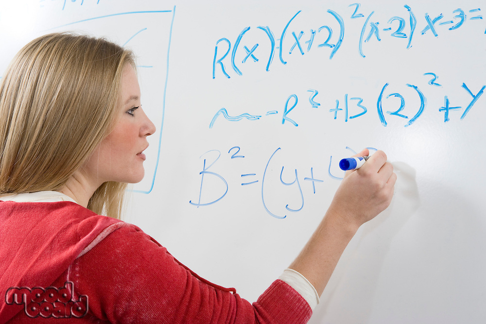 Female student writing maths equations on whiteboard
