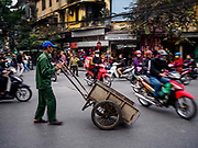 25 DECEMBER 2017 - HANOI, VIETNAM:  A man pushes a hand cart through traffic in Hanoi.    PHOTO BY JACK KURTZ