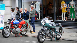 © Licensed to London News Pictures. 17/06/2018. LONDON, UK. Visitors view (L to R) an MV Agusta 750S motorcycle and a Ducati 750 SS 1974 motorcycle at the 6th Annual Classic and Supercar Pageant held at St John's Wood High Street.  Traditionally taking place on Fathers' Day, the show brings together an eclectic mix of exotic and popular vehicles attracting visitors young and old and raises funds for the local charity, The St John's Hospice.  Photo credit: Stephen Chung/LNP