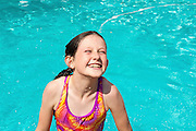 Delighted girl in a swimming pool.