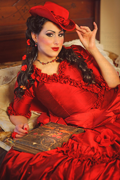 A tan young woman with red lipstick and a fancy historical dress in an old-fashioned bedroom with a journal on the bed