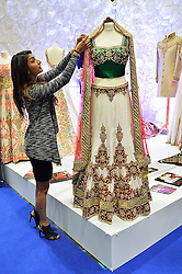 © Licensed to London News Pictures. 27/03/2016. A stand owner adjust a wedding dress at the Asian Bride Live Wedding Show featuring fashion, beauty and services for brides to be. London, UK. Photo credit: Ray Tang/LNP