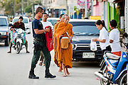 "25 SEPTEMBER 2009 -- PATTANI, THAILAND: A Buddhist monk on his morning rounds with an armed escort. Monks have been frequent targets of Muslim extremists and seldom go out without an armed escort. Thailand's three southern most provinces; Yala, Pattani and Narathiwat are often called ""restive"" and a decades long Muslim insurgency has gained traction recently. Nearly 4,000 people have been killed since 2004. The three southern provinces are under emergency control and there are more than 60,000 Thai military, police and paramilitary militia forces trying to keep the peace battling insurgents who favor car bombs and assassination.  PHOTO BY JACK KURTZ"