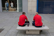 During the UK's Coronavirus pandemic lockdown and on the day when a further 255 deaths occurred, bringing the official covid deaths to 37,048, <br /> two workmen in matching shirts sit and talk close to each other on an empty Oxford Street, on 26th May 2020, in London, England.