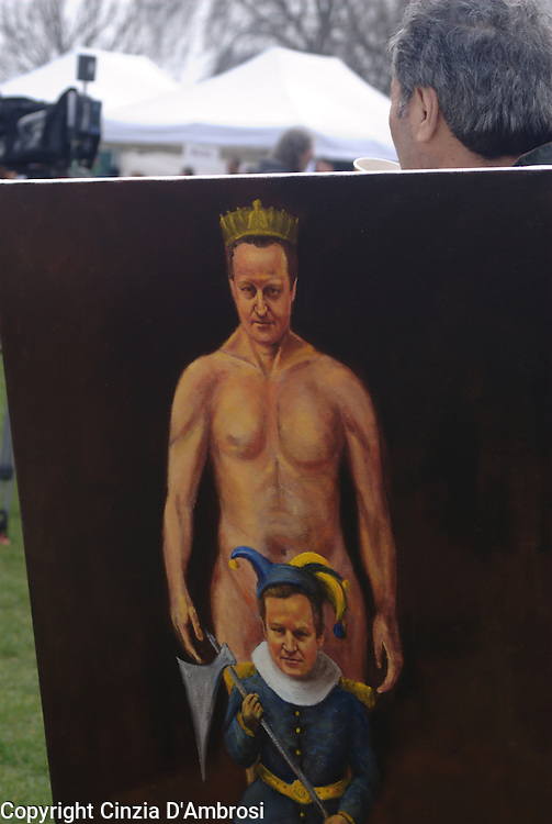 A demonstrator in a rally in Hyde Park holding a painting in which it is depicted the Prime Minister David Cameron, a satirical image that shows the way the people are viewing the minister massive cuts in the public sector.