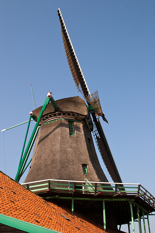 """The de Zoeker (""""The Seeker"""" wndmill, built almost enirely of wood in 1607 and still working. Zaanse Schans is a popular day trip for Amsterdam visitors.  .From Wikipedia: """" Zaanse Schans is a neighbourhood of Zaandam, near Zaandijk in the municipality of Zaanstad in the Netherlands, in the province of North Holland. It has a collection of well-preserved historic windmills and houses; the ca. 35 houses from all over the Zaanstreek were moved to the museum area in the 1970s. The Zaans Museum, established in 1994, is located in the Zaanse Schans..The Zaanse Schans is one of the popular tourist attractions of the region and an anchor point of ERIH, the European Route of Industrial Heritage. The neighbourhood attracts approximately 900,000 visitors every year..The windmills were built after 1574."""".Also from Wikipedia: """" Along the river Zaan, you can find still dozens of original windmills (mostly entirely made of wood), still technically functioning, some of them over 350 years old. Next to these there are many 19th century stone industrial buildings, nowadays derelict or converted into apartments, but still recognisable as industrial buildings.""""."""