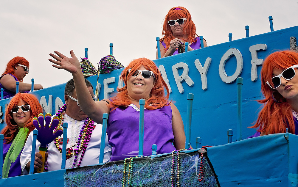 Float riders wave to the crowd as they participate in the Krewe de la Dauphine Mardi Gras Parade, Jan. 28, 2017, in Dauphin Island, Alabama. The theme of the parade was famous couples. This float paid homage to the Flinstones. (Photo by Carmen K. Sisson/Cloudybright)