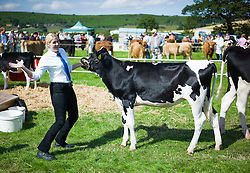 © Licensed to London News Pictures.12/08/15<br /> Danby, UK. <br /> <br /> A woman reacts to the camera as she prepares to lead her cow into the arena for an event at the 155th Danby Agricultural Show in the Esk Valley in North Yorkshire. <br /> <br /> The popular agricultural show attracts competitors and visitors from all over the surrounding area to this annual showcase of country life. <br /> <br /> Photo credit : Ian Forsyth/LNP