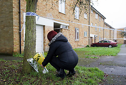 © London News Pictures. 12/11/2011. London, UK. A woman laying flowers outside a flat on Coronation Square in Reading, Berkshire sealed off by police today (12/11/2011) where the body of a 38-year-old woman was found. A 46-year-old man is currently in police custody  after he handed himself into a police station and pointed detectives to the body . Photo Credit : Ben Cawthra/LNP