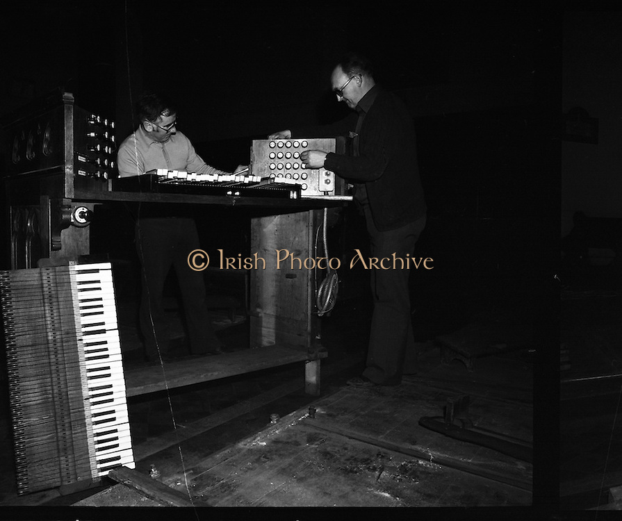 Pipe Organ Dismantling at Aungier Street.  (K86).1977..01.02.1977..02.01.1977..1st February 1977..A pipe organ built around 100 years ago for St Peter's Church (Church of Ireland),at Whitefriar / Aungier Street was being dismantled by Mr Gerry Smith and Mr Sam Wright of Dublin Organ Works. The organ was being dismantled for transfer to St Michael's Church,(Roman Catholic),in Blackrock,Co Cork..Image shows the delicate operation of dismantling of the organ keyboard.