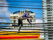 30 MAY 2015 - BANGKOK, THAILAND:  A worker for a local electrical utility strings power lines by walking along existing power lines along Ekkamai Soi 63 in Bangkok.  Most of the electricity consumed in Bangkok is generated in Laos and Myanmar. In 2013, the Bangkok Metropolitan Region consumed about 40 per cent of the Thailand's electricity, even though the BMR is only 1.5 per cent of the country's land area and about 22 per cent of its population.    PHOTO BY JACK KURTZ