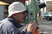 male surveyor looking through his Lieca optical tool