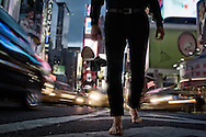 Barefoot man walking at night holding empty glass. Time Square. Manhattan.
