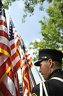 Firefighter band member holding American Flags during ceremony following Merrick Memorial Day Parade on May 28, 2012, on Long Island, New York, USA. America's war heroes are honored on this National Holiday.