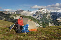 Adult male hiker in red shirt at backcountry camp on Red Face Mountain, Eiley-Wiley Ridge  seen in the distance, North Cascades National Park Washington
