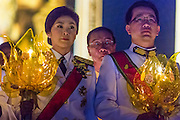 05 DECEMBER 2013 - BANGKOK, THAILAND: YINGLUCK SHINAWATRA (left), the Prime Minister of Thailand, and ANUSORN AMORNCHAT, her husband, (right) hold candles during the celebration of the birthday of the King in Bangkok. Thais observed the 86th birthday of Bhumibol Adulyadej, the King of Thailand, their revered King on Thursday. They held candlelight services throughout the country. The political protests that have gripped Bangkok were on hold for the day, although protestors did hold their own observances of the holiday. Thousands of people attended the government celebration of the day on Sanam Luang, the large public space next to the Grand Palace in Bangkok.     PHOTO BY JACK KURTZ