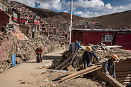For a story by Ed Wong : CHINASICHUAN - Two journals in Sichuan<br /> Larung Gar, Sertar, Sichuan, China<br /> October 8th, 2016<br /> A Buddhist monk walking past the ruins of dismantled cells while workers are dismantling another one. Thousands of monks and nuns from Tibetan regions and the rest of China, live and study in Larung Gar. Chinese authorities have requested that the number be reduced by 5000. The dismantling of cells where nuns and monks live, has begun.