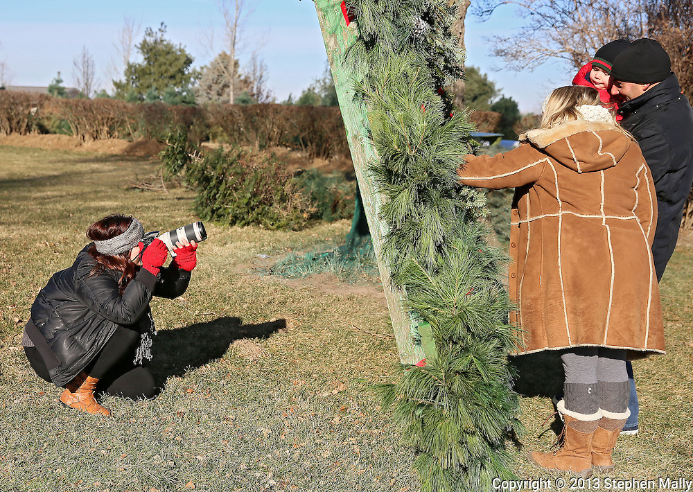 Robyn Rasmussen (from left) of Ruby Ellen Photography shoots through a set of Christmas wreaths during a family session with David and Jasmine Almeida of Iowa City along with their 2-year old son, Max, at Barnes Tree Farm in Iowa City on December 7, 2013.