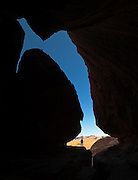 Ethan Welty stands in the mouth of a cave looking out towards the desert outside in Wadi Rum, Jordan.