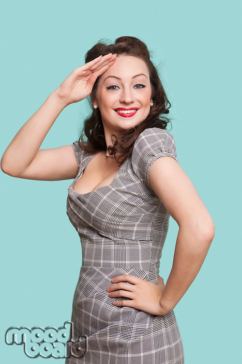 Portrait of beautiful young woman in dress saluting against blue background