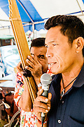 Man singing traditional songs accompanied by Khaen at Temple fair outside of Kumphawapi village, Udon Thani
