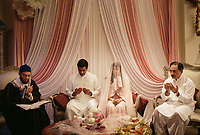 "At left, Imam Hisham Qaisi oversees the marriage of Adil Syed and Mavara Agha with her father Arif Agha, at right. The couple was married in the Mavara's childhood home in Oak Brook. Agha said that community ""in a religious and a cultural context is a huge part of a wedding…There are a lot of Pakistani Muslims in Oak Brook, and they all live pretty close to each other. Growing up we had a lot of get-togethers in my home, so having such a significant moment in my home and in front of my community meant a lot to me."" 