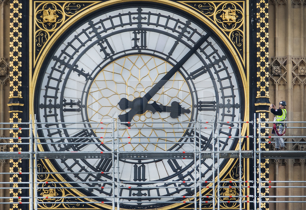 © Licensed to London News Pictures. 12/10/2017. London, UK. A scaffolder (R) takes a photo of a clock face on The Elizabeth Tower, known as Big Ben at Parliament. Scaffolding will reach a height of 96 meters when completed - the work is part of a three-year programme to conserve the Great Clock, the Elizabeth Tower and Big Ben. London, UK. Photo credit: Peter Macdiarmid/LNP