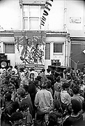Crowd by a sound system on All Saints Road in Notting Hill, once the most most CCTV'ed road in the UK, plays its music to the crowd in front of a banner depicting black people in front of the Union jack flag drenched in red symbolising blood as a reference to the treatment meted out to the afro Caribbean community by authority, Notting Hill Carnival, London, 1989