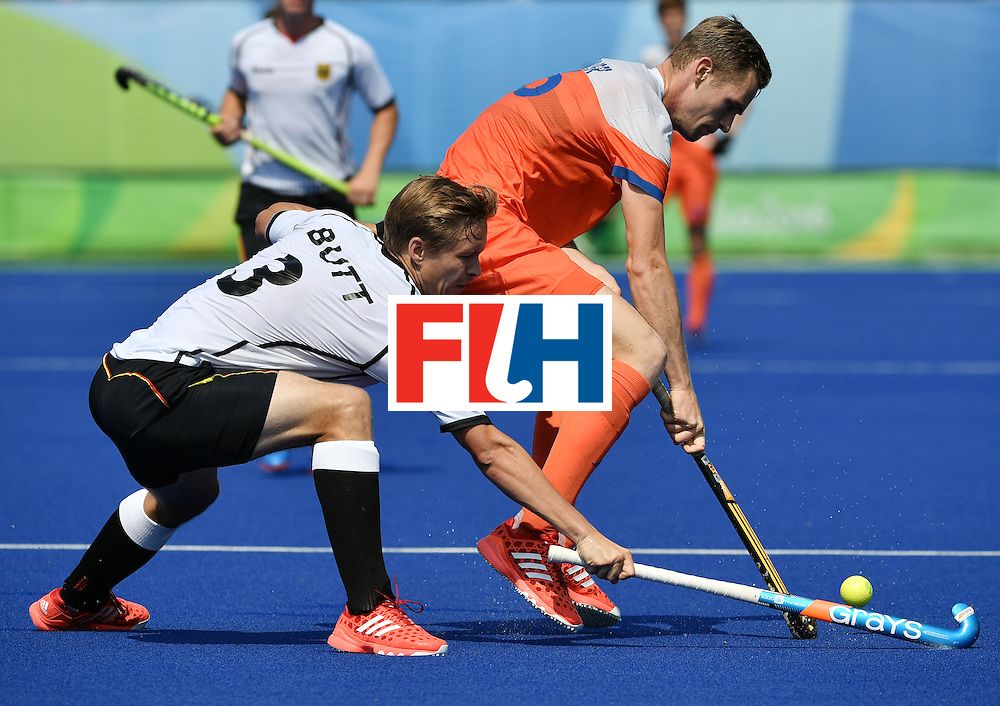 Germany's Linus Butt (L) and Netherlands' Mirco Pruijser vie for the ball during the men's Bronze medal field hockey Netherlands vs Germany match of the Rio 2016 Olympics Games at the Olympic Hockey Centre in Rio de Janeiro on August 18, 2016. / AFP / Pascal GUYOT        (Photo credit should read PASCAL GUYOT/AFP/Getty Images)