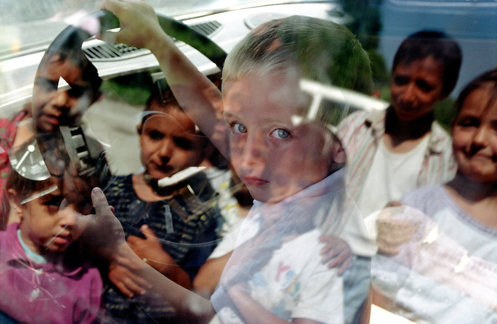 Daniela's son Razo plays in a car wreck left in front of the hotel where he lives, some of the other children watch from the outsides. 2003..Daniela and her son are refugees from Kosovo, they have lived in a hotel for mor ethan 6 years. .