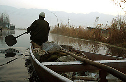 A Kashmiri man paddles to a floating market in the early freezing temperatures before sunrise on Dal Lake in the summer capital of Kashmir, Srinagar India, November 24, 2001. In the background, echoing through the nearby mountains, gunshots and fighting could be heard. Kashmir was once a tourist hotspot but now vendors struggle to survive in a place that has seen nearly 1000 civilians killed this year alone and 1,765 wounded in a brutal conflict that the United Nations calls the most dangerous place in the world.  (Photo by Ami Vitale/Getty Images)