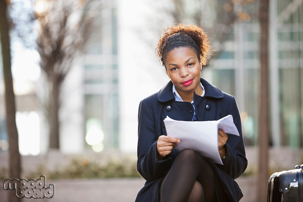 Portrait of confident African American young woman with documents sitting outdoors