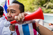 22 DECEMBER 2013 - BANGKOK, THAILAND: A protestor blows a horn on the street in front of the home of caretaker Prime Minister Yingluck Shinawatra. Hundreds of thousands of Thais gathered in Bangkok Sunday in a series of protests against the caretaker government of Yingluck Shinawatra. The protests are a continuation of protests that started in early November and have caused the dissolution of the Pheu Thai led government of Yingluck Shinawatra. Protestors congregated at home of Yingluck and launched a series of motorcades that effectively gridlocked the city. Yingluck was not home when protestors picketed her home.     PHOTO BY JACK KURTZ