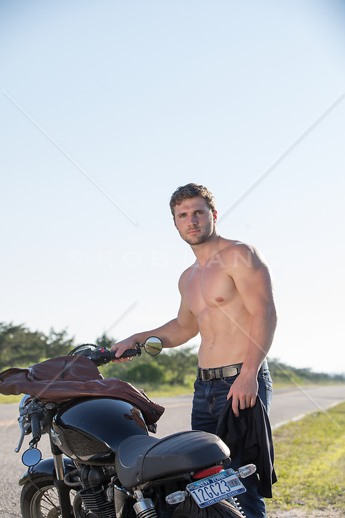 hot shirtless man by a motorcycle on a rural road
