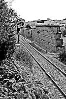 tratto del binario in prossimità di un passaggio a livello delle linee SUD EST; si notano da una parte la segnaletica ferroviaria e dall'altra le barriere anti rumore. Reportage che racconta le situazioni che si incontrano durante il viaggio lungo le linee ferroviarie SUD EST nel Salento.