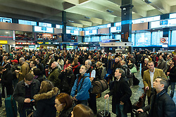 Holiday Travellers Train. Passengers wait for trains at Euston station, London. Heavy rain and strong winds of up to 80mph are expected to bring down overhead rail lines and lead to treacherous driving conditions on what will be a busy day ahead of the holiday.Euston Station, London, United Kingdom. Monday, 23rd December 2013. Picture by Peter Kollanyi / i-Images