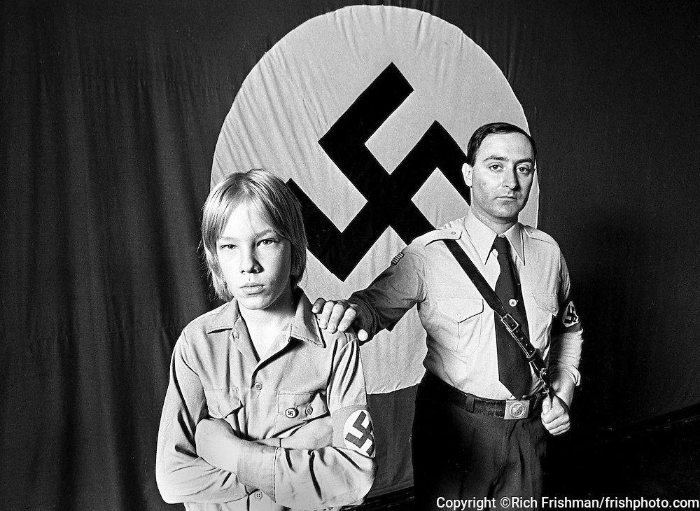Portrait of Nazi Party leader Frank Collin and a 10-year old disciple in full Nazi uniforms in front of a Swastika flag in the Chicago headquarters of the National Socialist Party of America..While president of the NSPA, Frank Collin was arrested by Michigan police while having sex with a pair of 10-year-old boys. It later was revealed that Collin was actually Jewish and was born with the name Francis Joseph Cohen..©Rich Frishman.