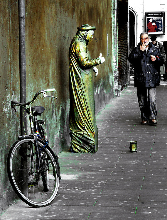 Mute mime (possibly a student)  in gold lame robes, in a sidewalk near Piazza Venezia, Rome. One hand held in front, thumb pointing upward.  Indifferent pedestrian, a man, walks by, his arm also up with a cigarette.  The mime's bicycle chained to pipe in the foreground, and a can for contributions in the ground in front.