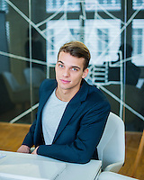 Portrait of confident young businessman sitting at conference table