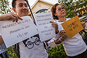 "12 JANUARY 2014 - BANGKOK, THAILAND:  Pro-democracy advocates hold up signs before a candlelight vigil at Thammasat University in Bangkok. About 500 people from all walks of Thai life came to a candlelight vigil at Thammasat University. They prayed for a peaceful resolution to the political conflict in Thailand. They finished the vigil by singing the John Lennon song ""Imagine."" Anti-government protestors are expected ""Shutdown Bangkok"" Monday. There were reports Sunday evening that some intersections were already being blocked.      PHOTO BY JACK KURTZ"