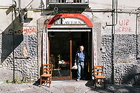 "NAPLES, ITALY - 10 OCTOBER 2018: A wine supplier of La Taverna a Santa Chiara is seen here at the entrance of the tavern in the historical center of Naples, Italy, on October 10th 2018.<br /> <br /> The idea of the founders Nives Monda and Potito Izzo (two really unusual names in southern Italy) was to create a ""taste gate"" of Campania products. La Taverna a Santa Chiara, founded in 2013, is a modern tavern whose strengths are the choice of regional and seasonal products and mostly small producers. Small restaurant, small producers.<br /> The two partners tried to put producers and consumers in direct contact, skipping the distribution, and managing to reduce the costs of the products considerably. Nives and Potito managed to create a simple kitchen, at moderate costs but with high quality raw materials.<br /> ""A different restaurant idea,"" says Nives, ""the producers deliver their products at low prices and the tavern manages to make traditional dishes with niche products"".<br /> Nives Monda has been a labor consultant for 20 years. Potito Izzo is the chef who has always been loyal to the  family cuisine. When he embraced the idea of Nives he found in the tavern the natural place to express the tradition of Neapolitan cuisine. Nives defines him as a ""comfort food chef"". Their partnership is a true friendship that has lasted for over 10 years."