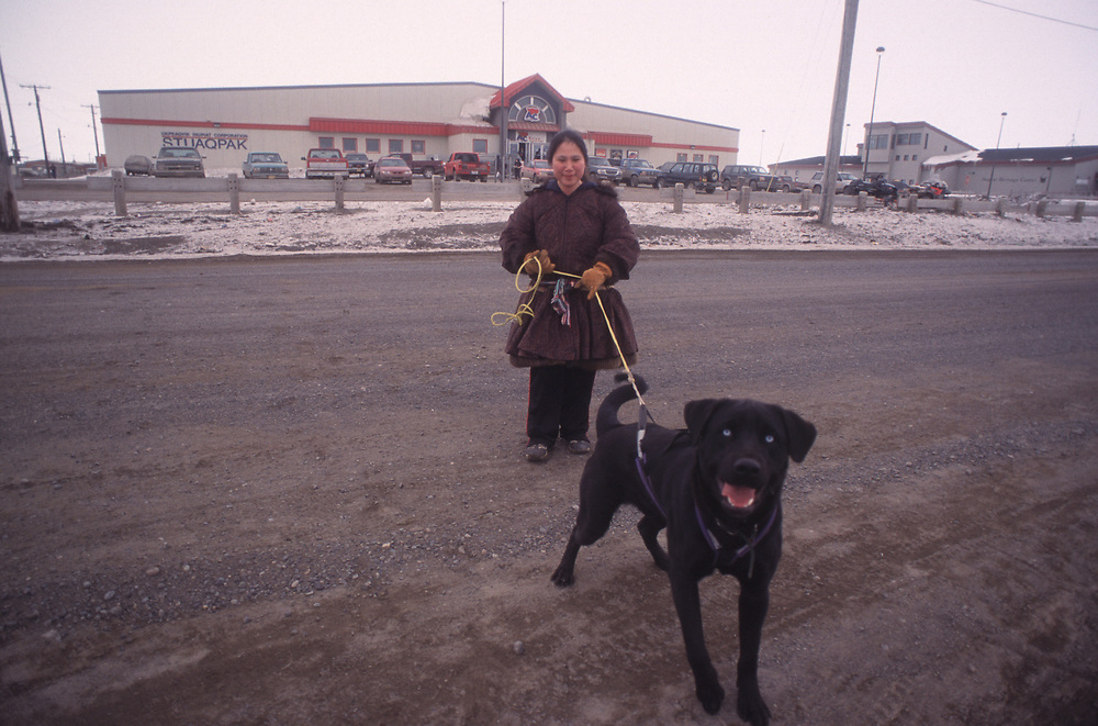 Fannie Hopson walking her labrador-husky mix dog, Killer. In spite of his name, Killer is a nice dog and got very scared with the click of my camera.  Behind them is the store or Stuaqpak where you can buy mainly everything from four-wheelers or couches to lettuce and fabric.<br /> <br /> May 14, 19:37