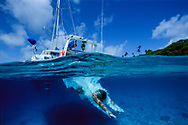 Enjoying the pleasures of barefoot sailing charter in crisp clear Tongan waters. South Pacific.