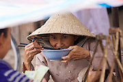 At the market. Woman eating rice.