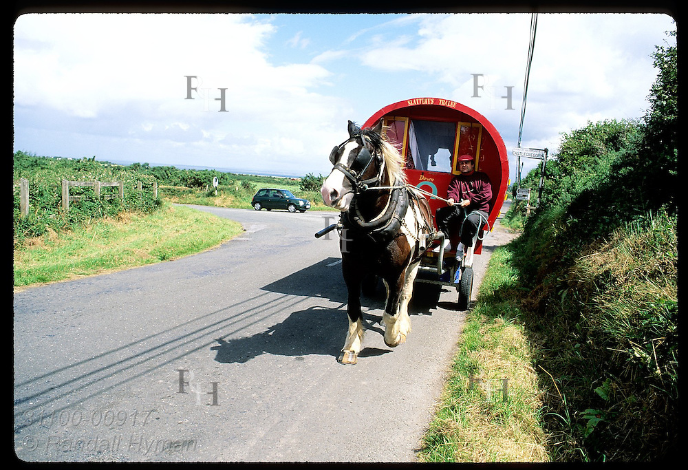 Man on vacation drives his live-in, horse-drawn trailer along road on Dingle Peninsula. Ireland